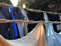 Don't forget to floss  - An image of a clothes' line in a public laundry in Walkeshwar with a tooth brush stuck in it