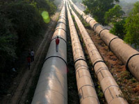 Life line - An image of water pipes and a man Walking on them in Mumbai