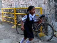 Girl and bicycle - An image of a girl running with a bicycle in the background