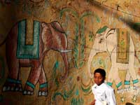 Elephants and boy - An image of a boy running with a painting of elephants on a wall in the background
